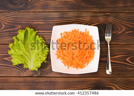 plate with carrot with salad leaf. flat lay. top view - stock photo