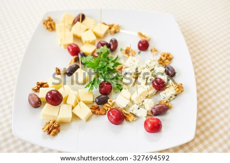 Plate with Cheeses and Olives - stock photo