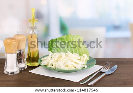 Plate with coleslaw and seasonings on wooden table on room background