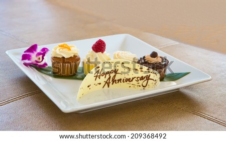 Plate with Desserts and a chocolate Banner saying Happy Anniversary - stock photo