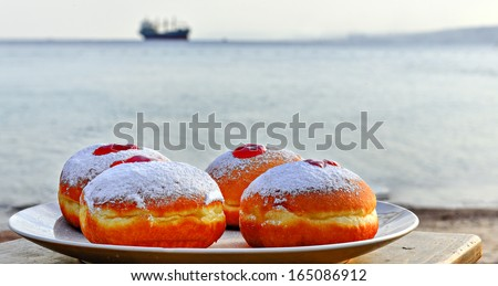 Plate with donuts on background of the Red Sea, Israel  - stock photo