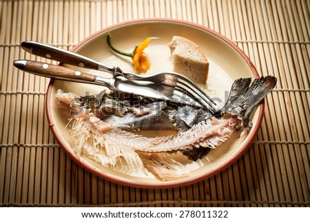 plate with food leftover bones of fish - arranged food - stock photo
