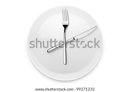 plate with fork and knife at twelve o'clock position, on white background - stock photo
