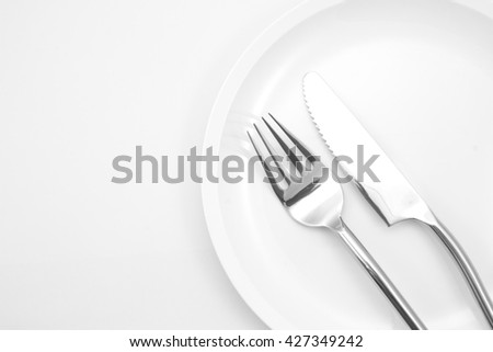 plate with fork and knife on a white background