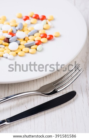 Plate with fork, knife and colorful pills