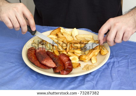 Plate with french fries and sausages on the plate and male hands with fork and knife