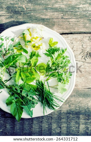 Plate with Fresh Green Leaves on Wooden Table. Natural decoration of Easter eggs - stock photo