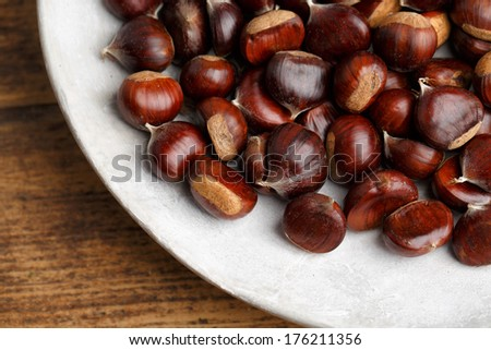 Plate with fresh Sweet Chestnuts from the Forest in Autumn