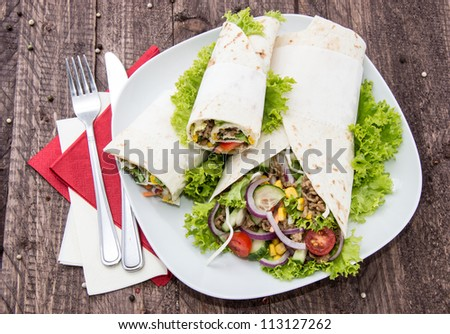 Plate with fresh Wraps on wooden background
