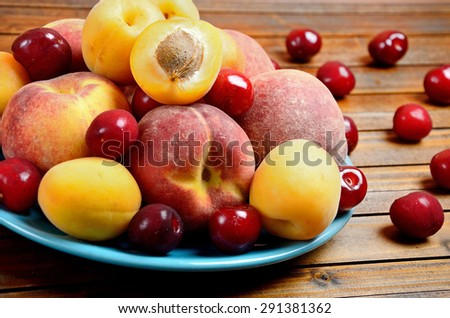 Plate with fruits on wooden table - stock photo