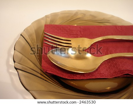 plate with golden fork and spoon on red serviette - stock photo