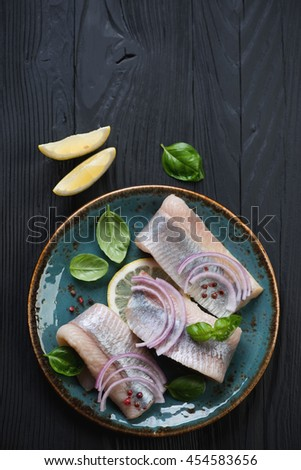 Plate with herring fillet on a black wooden surface, top view