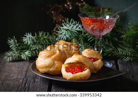 Plate with Home made Profiteroles stuffed by red caviar with glass vase of red caviar and Christmas tree at background over old wooden table. Dark rustic style - stock photo