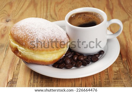 Plate with homemade donut and coffee cup on old wooden table - stock photo