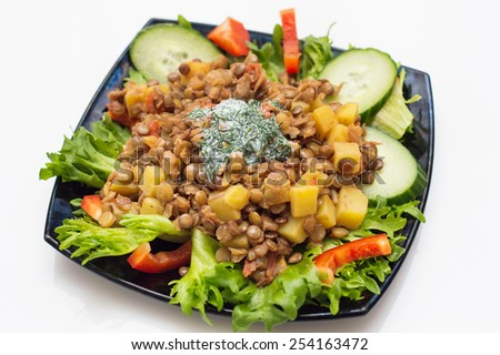 Plate with homemade tasty vegan vegetable meal from potatoes, salad, tomatoes, paprika, onion and lentil with white dill sauce - stock photo
