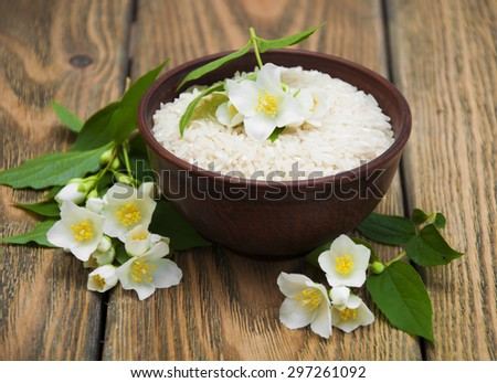 Plate with jasmine rice and jasmine flowers on a wooden background - stock photo