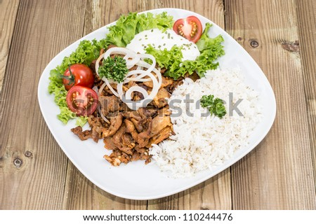 Plate with Kebab and Rice on wooden background - stock photo