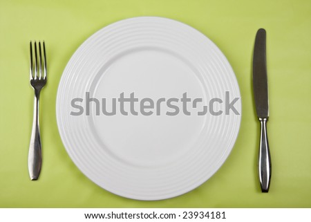 plate with knife and fork on green background - stock photo