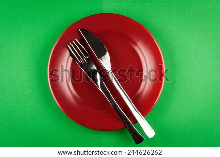 plate with knife and fork on green table