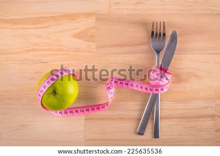 Plate with measure tape, knife and fork. Diet food on wooden table. apple and measuring tape on the floor scales isolated on white - stock photo