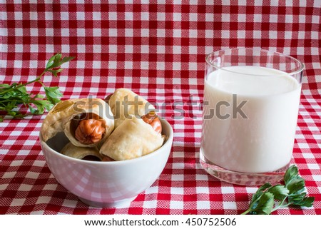 Plate with mini hot dogs homemade (Sausage in the dough) and a glass of fresh cow's milk with parsley on a plaid background. On July 18, America celebrates the Day of Hot Dog. - stock photo