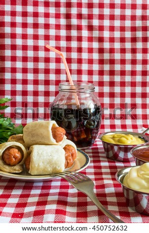 Plate with mini hot dogs with sauces: mustard, ketchup, mayonnaise and cola. In Europe, prepare mini hot dogs and fall with various sauces. On July 18 at America celebrate the Day of Hot Dog. - stock photo