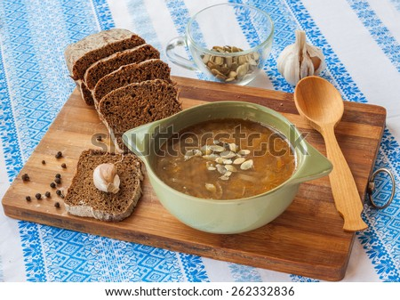 Plate with pumpkin soup with fried onions and meat close to the pot and pieces of rye bread - stock photo