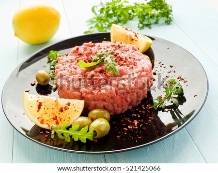 Plate with raw beef tartar with olives, lemon and herbs. Shallow dof.