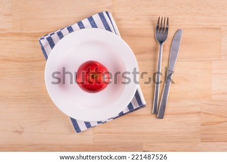 plate with red apple, knife and fork on white brown wooden table. Healthy Diet concept. Above view - stock photo