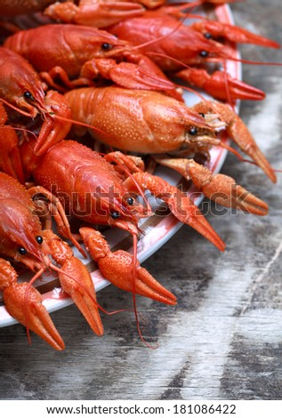Plate with red boiled crawfish on a wooden table in rustic style, close-up, selective focus on one crawfish - stock photo