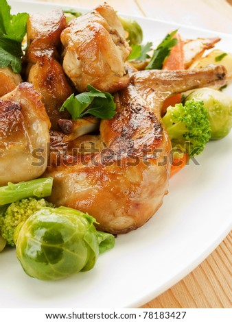 Plate with roasted rabbit and vegetable garnish. Shallow dof. - stock photo