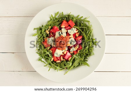 Plate with rucola salad, mildew cheese, red paprika and pesto - stock photo