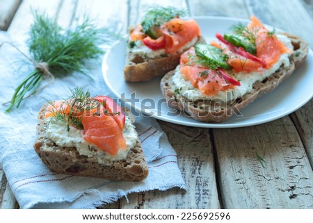 Plate with sandwiches with salmon on a wooden table boards - stock photo