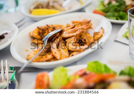 Plate with seafood. Appetizing dish with cooked shrimp. Delicious protein meal. Shrimp, seafood, herbs, Italian cuisine. - stock photo