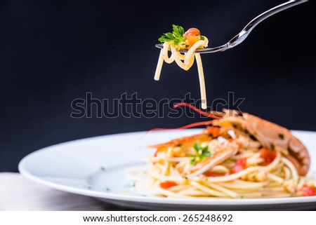 Plate with seafood spaghetti pasta on fork.Italian restaurant menu plate, noodles with prawns, langoustines, lobster.Italian food background. - stock photo
