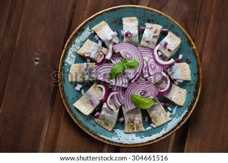 Plate with sliced herring filet, dark wooden surface, above view - stock photo