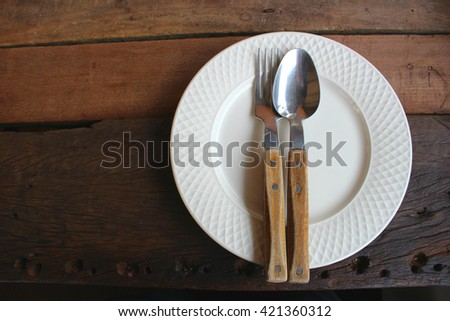 Plate with spoon and fork with wood background  processed in dark tone  - stock photo