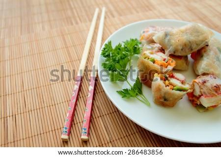 Plate with spring rolls with vegetables, chicken and crab sticks - stock photo