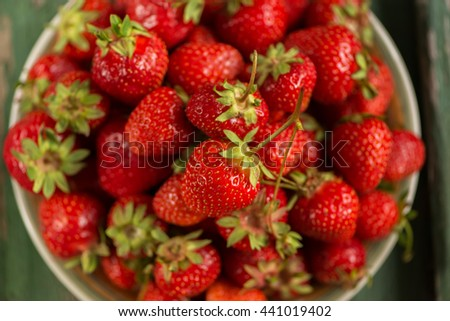 Plate with strawberries on a background of an old green wooden table