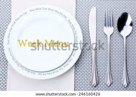 "Plate with text ""Week Menu"", fork, knife and spoon on tablecloth background"