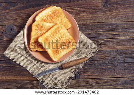 Plate with toasted bread and knife on wooden table, top view