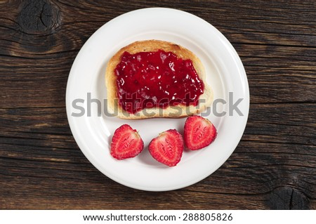 Plate with toasted bread with jam and strawberry on dark wooden table, top view - stock photo