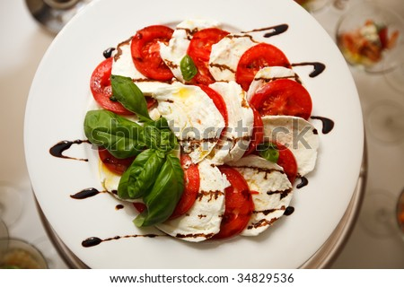 Plate with tomatoes and Mozzarella. Looks tasty and elegant - stock photo
