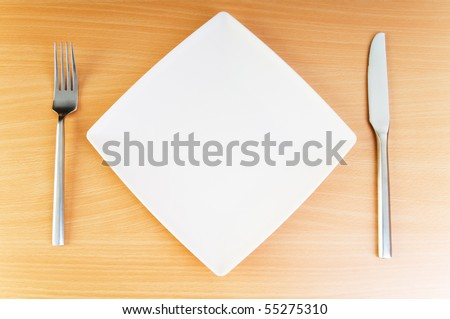 Plate with utensils on wooden table
