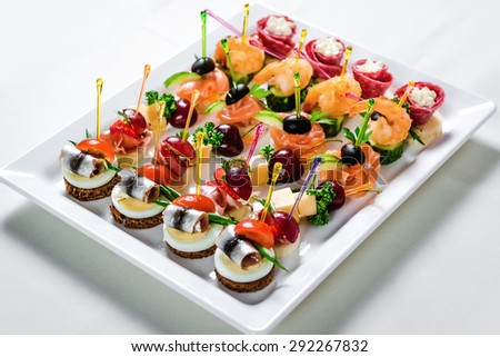 Plate with various seafood and meat canapes. Pickled herring with egg, cheese and cherry,  salmon, prawns with cucumber and stuffed salami - stock photo