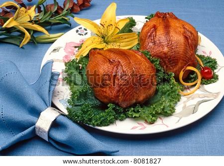 Plated Cornish Game hens with flower garnish - stock photo