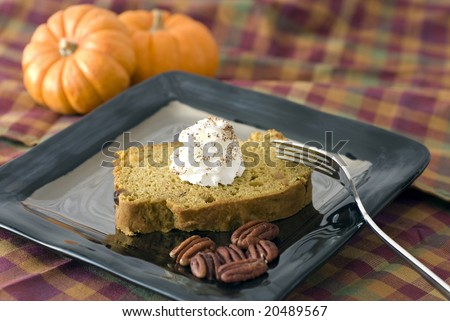Plated quick pumpkin bread with a dollop of whipped cream, spiced with nutmeg.  Pecans in the foreground of the plate and mini pumpkins in the background.  Harvest colored fabric background. - stock photo
