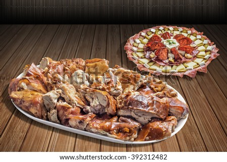 Plateful of Spit Roasted Pork Slices and Serbian Traditional Appetizer Meze Set on Bamboo Place Mat Surface - stock photo