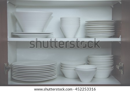 Plates and bowls in cupboard - stock photo