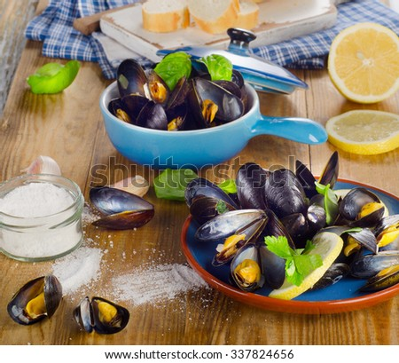 Plates of steamed mussels on a wooden background.  - stock photo